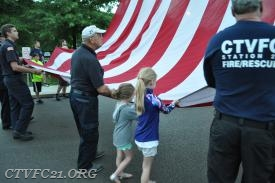 Past President Chris DeCree receives assistance from our guests in raising the flag.